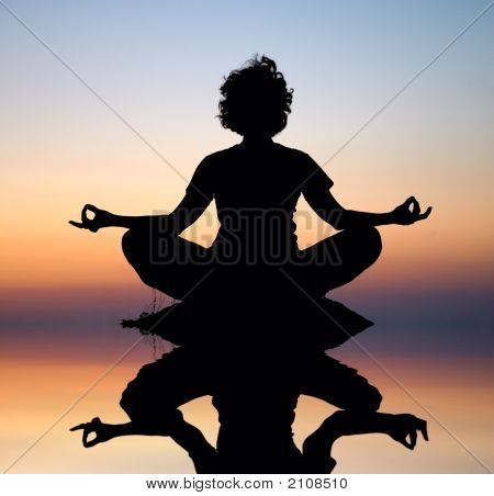 Evening Yoga Meditation In Padmasana On Stone Over Water