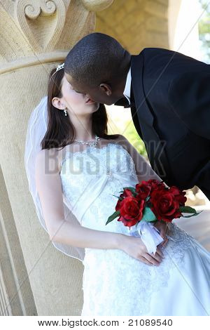 An  african man and caucasian woman wedding couple kissing outside church