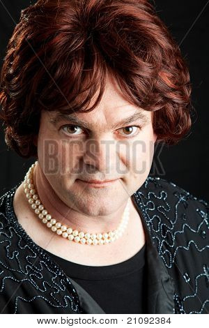 Drag queen dressed as a female celebrity.  Portrait on black background.