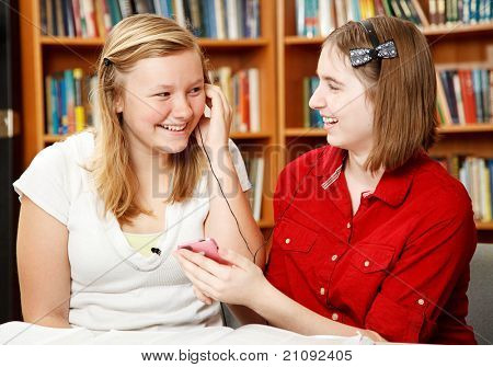 Teen girls in the school library listening to an mp3 player.