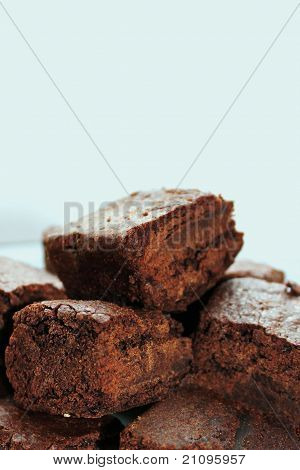 Pile of tasty chocolate brownies on white background