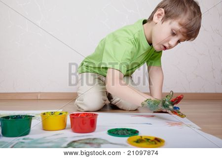 Boy in the green t-shirt draws color paints with his fingers on the sheet of paper