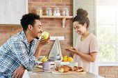Glad Female Makes Sandwich, Talks With Husband Who Sits Opposite Her, Eats Apple. Family Couple Spen poster