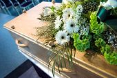 stock photo of mortuary  - A coffin with a flower arrangement at a mortuary