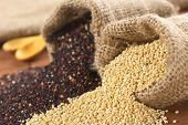 stock photo of quinoa  - Raw red and white quinoa grains in jute sack on wood - JPG