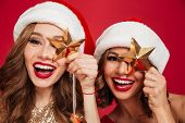 Close up portrait of a happy smiling women in christmas hats holding golden stars and looking at cam poster