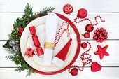 Christmas dinner table setting with porcelain plates, serviette, red decorations with holly, mistlet poster