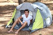 Teenage boy sat in tent