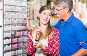 Couple, woman and man, choosing color of wall paint in decoration department of hardware store poster