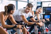 Young people talking and smiling while working out on bike at gym. Friends in a conversation while c poster