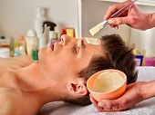 Mud facial mask of man in spa salon. Massage with clay full face. Guy in therapy room. Man lying spa poster