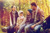 camping, travel, tourism, hike and people concept - happy family sitting on bench and talking at cam poster