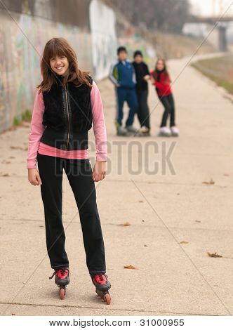 Pretty smiling girl posing outside with friends in the background on cloudy autumn day