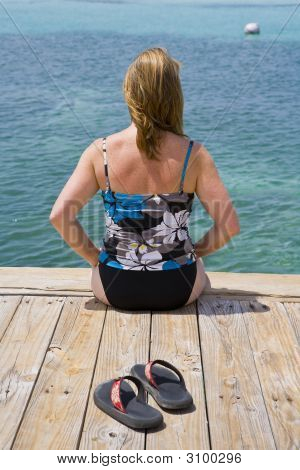 Woman Sitting On A Caribbean Dock