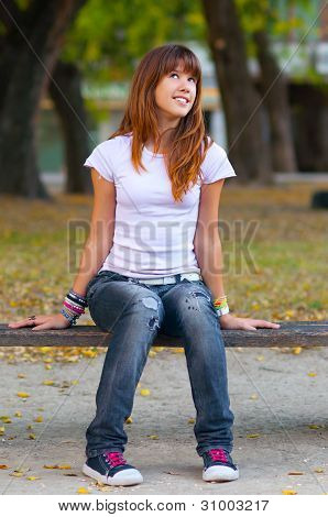 Beautiful teenage girl in fashionable warn out jeans, t-shirt and sneakers smiles while watching the