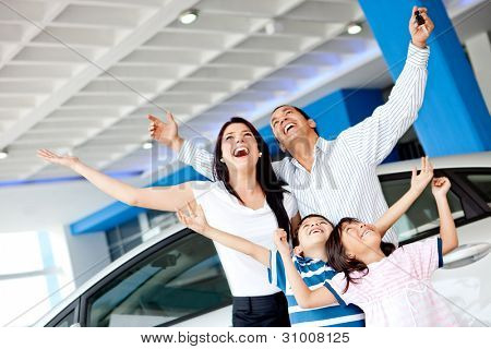 Excited family at the dealer buying a car and celebrating