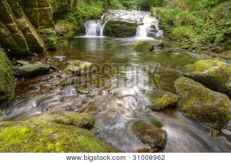 Stunning Waterfall Flowing Over Rocks Through Lush Green Forest With Long Exposure