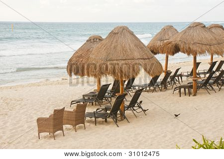 Wicker And Rattan Chairs Under Thatched Huts On Beach