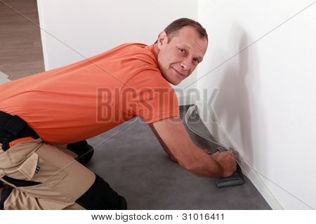 Man laying a linoleum floor