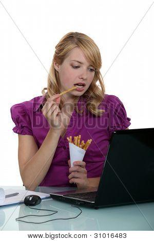 Frau Schreiber Essen Pommes frites an ihrem Schreibtisch