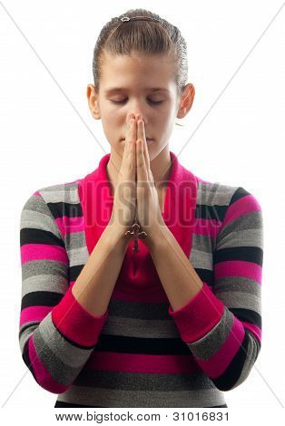 Beautiful young girl praying while holding small leather cross between her palms