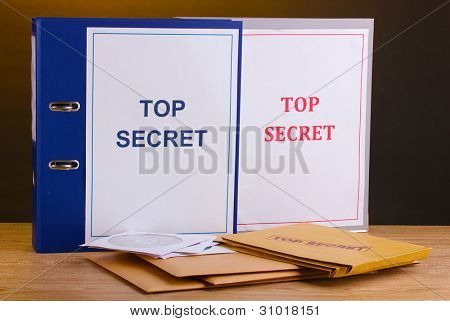 Envelopes and folders with top secret stamp and  CD disks on wooden table on brown background
