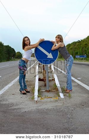 Two Pretty Girls Stand On A Road
