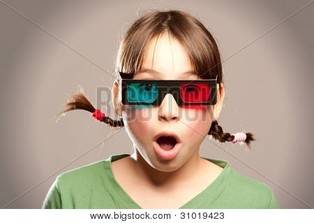 young girl watching a movie wearing 3d glasses