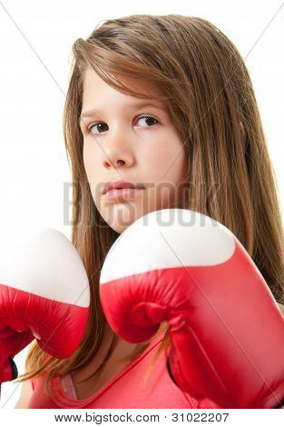 Pretty teenage girl posing with boxing gloves isolated on white
