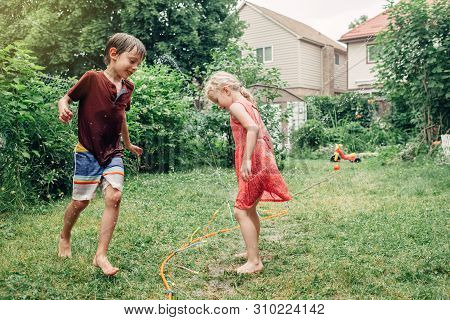 poster of Kids Friends Boy Girl Splashing With Gardening Hose Sprinkler On Backyard On Summer Day. Children Pl
