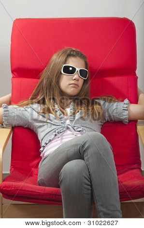 Pretty young teenage girl resting in the red chair with sunglasses on her head