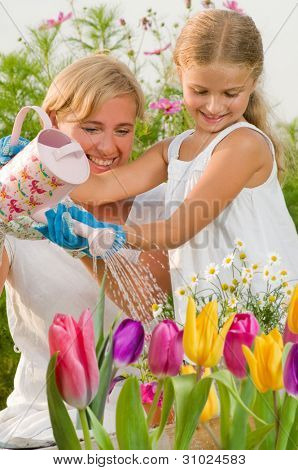 Spring garden - mother with daughter watering flowers in the garden