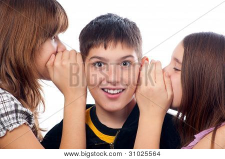 Two girls and a boy gossiping isolated on white background