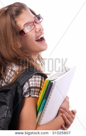 Pretty teenage girl posing with school bag on her shoulder and notebooks in her hands