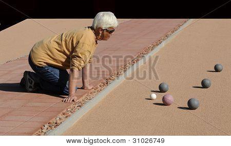 Mujer Senior estudiar bolas de petanca en la cancha de la arena