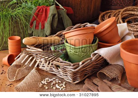 Gardening still life with flower pots, gardening tools, and plants in wicker baskets with burlap and rope.