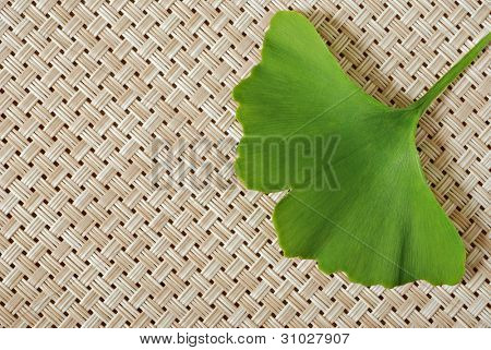 Ginkgo leaf on wicker background with copy space.