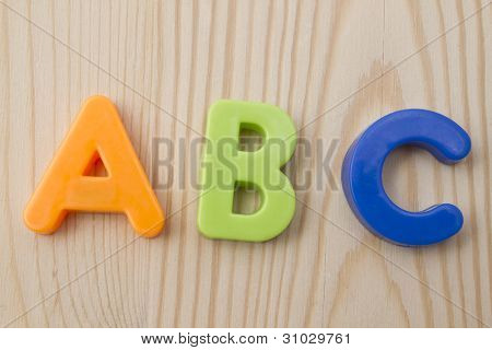 Letter magnets A B C closeup on wood background