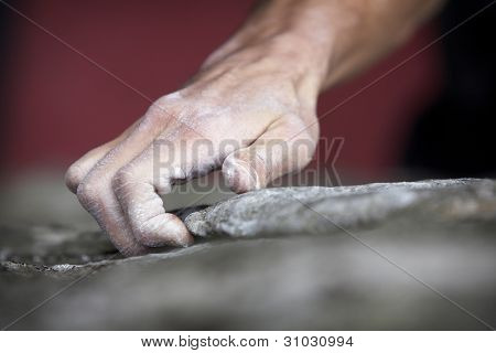 Grabbing onto a small handhold, a climber makes his way to the top. His hand is covered in chalk, and there is a very shallow depth of field.