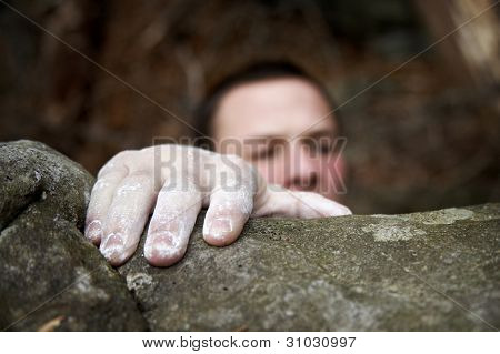 A climber reaches the top of a boulder. His visible hand is covered in white chalk, and his face is just peeking over the edge.