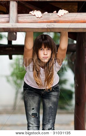Pretty teenage girl in fashionable jeans and t-shirt poses while holding wooden bar