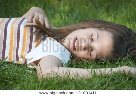 Pretty young teenage girl resting on the bed of grass