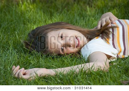 Pretty young teenage girl resting on the bed of grass and smiling