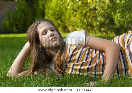 Pretty young teenage girl resting on the bed of grass and enjoying beautiful day