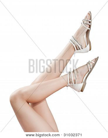 Beautiful women legs in sandals up in the air isolated on the white background.