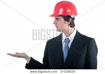 Young engineer with red helmet holding imagined object on his open palm isolated on white