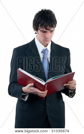 Businessman reading the big red book isolated on white