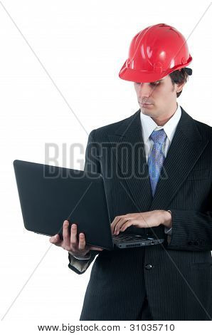 Young engineer with red helmet working on the notebook isolated on white