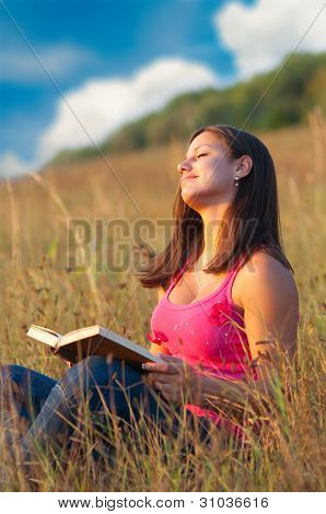 Beautiful young girl enjoys sun while sitting on the meadow and reading the book
