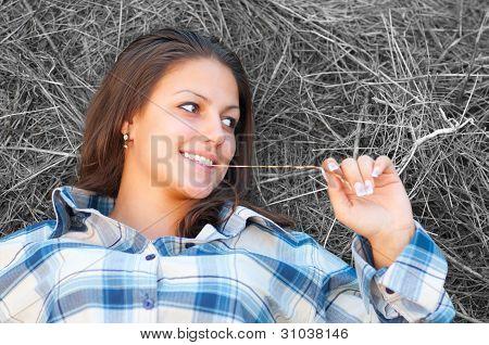schöne junge Frauen liegt auf den Haufen Heu und lächelt